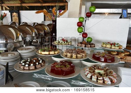 Jello decorated with Kiwi slices, chocolate cake, cheesecake and fruit on the dessert buffet at an all inclusive Mexican resort.
