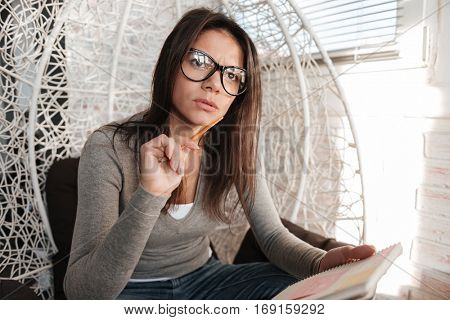 Image of young woman wearing eyeglasses sitting on chair indoors while writing notes in notebook. Look aside.
