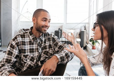 Picture of smiling business partners in office working with documents on floor. Focus on man. Look at each other.