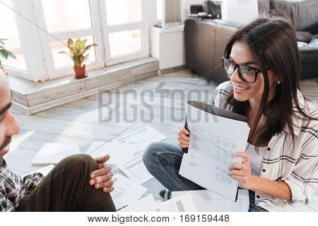 Photo of happy business partners in office working with documents on floor. Focus on woman. Look at each other.