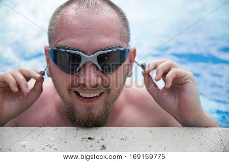 Active man smiliing in blue water on vacation