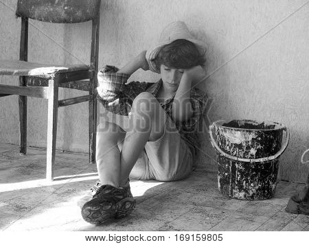 Child labour concept. Tired boy painter is very tired after work.Tired schoolchild in shirt sleeping on the floor. Black and white photo. Children worker. Stop child labour