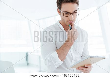Image of young concentrated man dressed in white shirt writing notes in notebook. Looking at notebook.