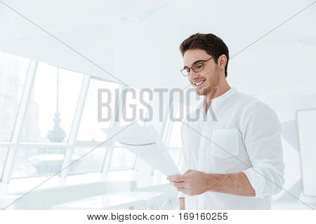 Image of happy young man dressed in white shirt standing near big white window while holding documents.