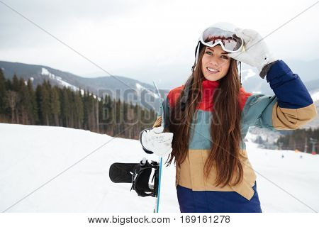 Picture of happy young lady snowboarder on the slopes frosty winter day. Look at camera.