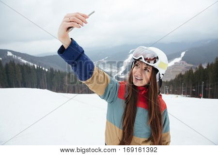 Image of young woman snowboarder on the slopes frosty winter day making selfie by the phone. Look at phone.