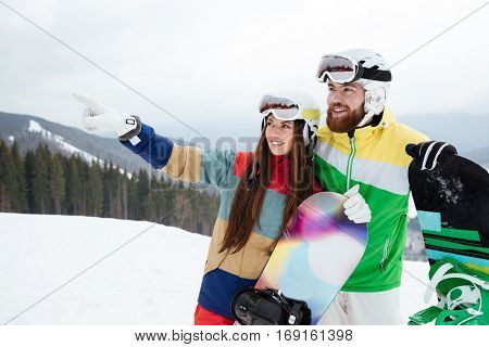 Photo of loving couple snowboarders on the slopes frosty winter day pointing. Look aside.