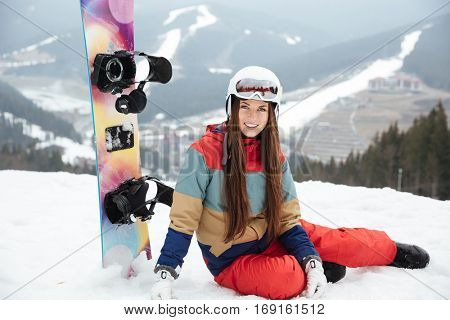 Picture of pretty lady snowboarder on the slopes frosty winter day. Look at camera.