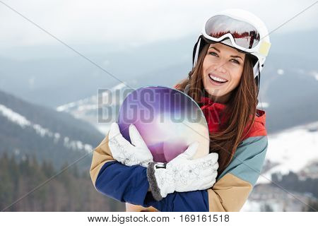 Picture of happy lady snowboarder on the slopes frosty winter day holding snowboard in hands. Look at camera.