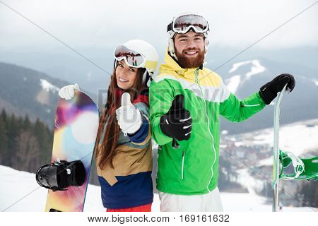 Photo of cheerful loving couple snowboarders on the slopes frosty winter day making thumbs up gesture. Look at camera.