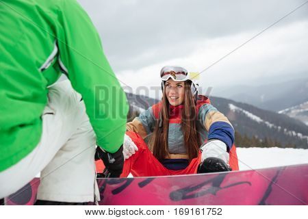 Photo of young loving couple snowboarders on the slopes frosty winter day. Look at each other. Focus on woman.
