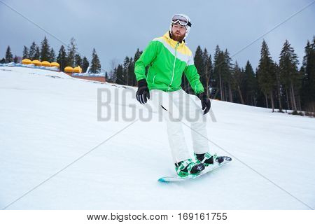 Photo of young man snowboarder on the slopes frosty winter day. Look aside.