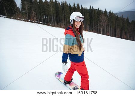 Photo of young cheerful lady snowboarder on the slopes frosty winter day. Look aside.
