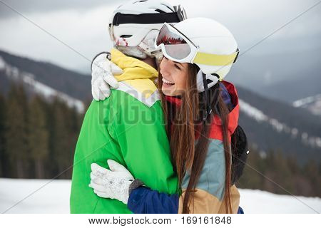 Image of loving couple snowboarders on the slopes frosty winter day hugging. Look aside.