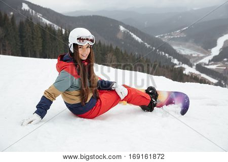 Image of young pretty lady snowboarder lies on the slopes frosty winter day. Look at camera.
