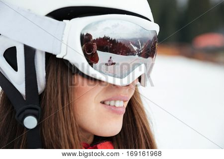 Portrait of beautiful woman snowboarder on the slopes frosty winter day. Look aside.