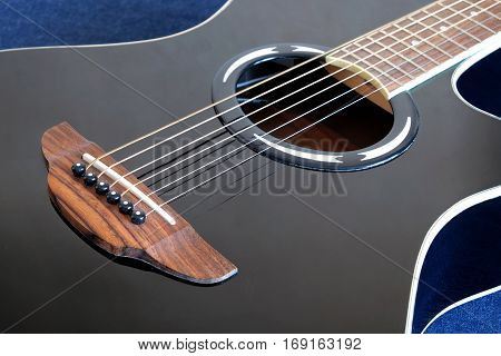 Classic acoustic six strings guitar black color top with cutaway fragment on jeans background side view closeup