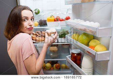 Young woman in the sleepwear eating sweet donuts near the refrigerator