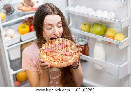Young woman with pizza standing near the open refrigerator full of fruits and vegetales