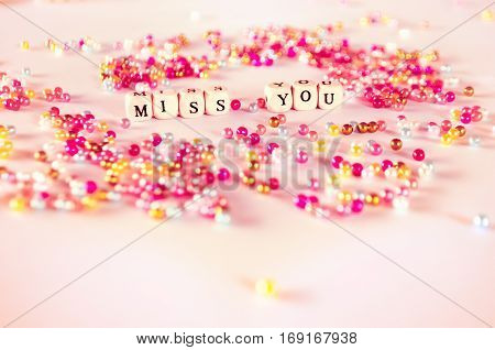 Miss you text with multicolor beads with pinkish ambient.