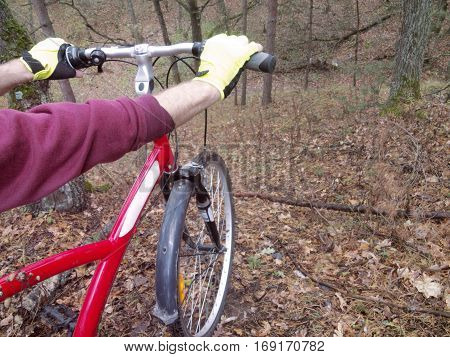 man's hands in bright cycling gloves tightly holding the straight handlebar of the bicycle