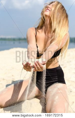 Cheerful blonde in black lingerie sifts the sand through her fingers on the beach.