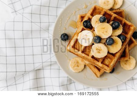 Homemade Belgian Waffles with milk and honey on table. Delicious breakfast