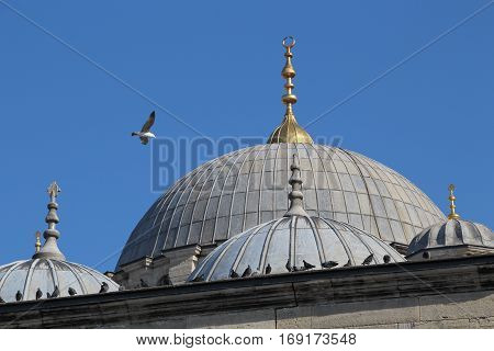 Large dome and three semi-domes with finials, New Mosque, Istanbul, Turkey against blue sky, copy space