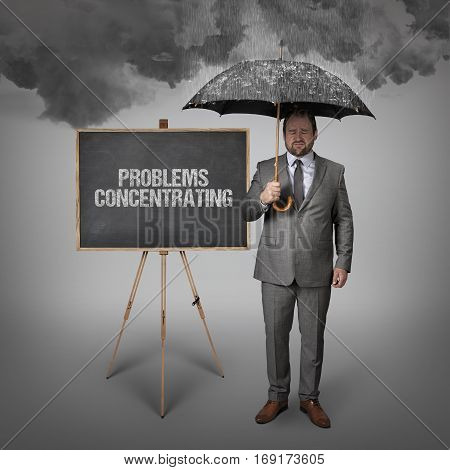 problems concentrating text on blackboard with businessman holding umbrella