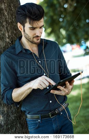Casual young man using tablet in park.