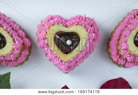 Heart shaped cupcake with pink icing and ganache filling garnished with red roses.