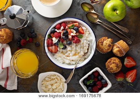 Breakfast table with rice pudding, fresh fruit and muffins overhead shot