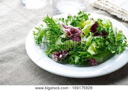Green salad with spinach, frisee, arugula and radicchio on blue wooden background, horizontal