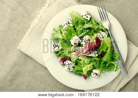 Green salad with spinach, frisee, arugula, radicchio, feta cheese and black sesame seed on blue wooden background, toned, top view