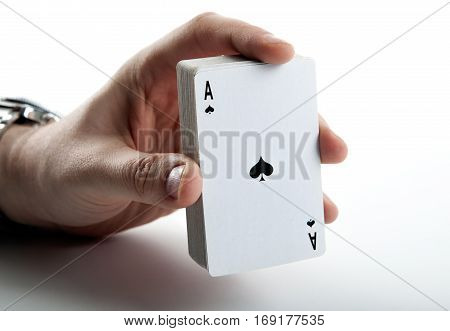 Human hand holding the ace of spades and a deck of cards close up