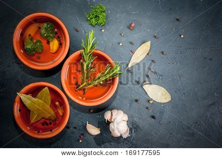 Selection of scented oils from herbs and spices: rosemary garlic pepper parsley bay leaf. On a dark gray stone kitchen table. Top view copy space