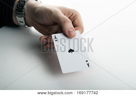Human hand holding the ace of spades close up