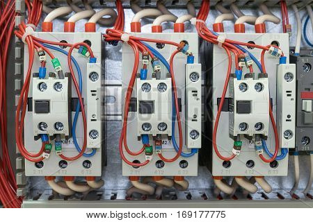 Power contactors with front auxiliary contacts mounted on the rail on the artboard. Wires with ferrules are connected to the contactors. The markings on the wires. Removed the wires in the cable channels.