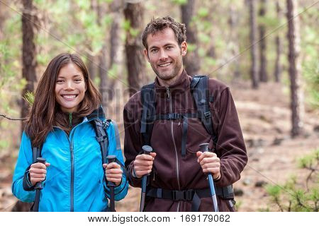 Happy young multiracial people hiking outdoors in nature forest. Healthy couple multiethnic group. Smiling Asian woman and Caucasian man in autumn.