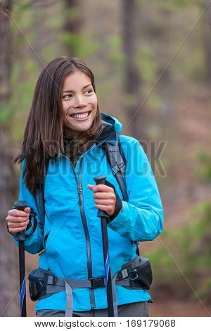 Happy Asian hiker girl in nature forest with backpack and hiking poles walking alone in woods. Healthy smile Chinese woman tourist.