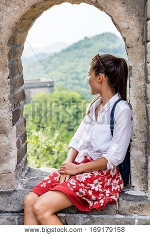 China travel at Great Wall. Tourist woman in Asia relaxing sitting on famous Chinese tourist destination and attraction in Badaling north of Beijing. Resting traveler hiking great wall on vacation.