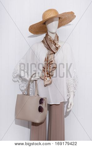 female clothing with hat and scarf, bag, sunglasses on mannequin-wooden background