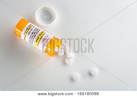 Non-Proprietary Medicine Prescription Bottle and Spilled Pills Over Head on Grey Background. This label contains only fictitious information.