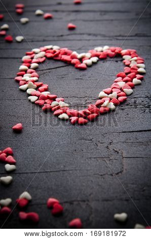 Heart made with small candy hearts, pink, red, whie colors, on dark background. Love, Valentine's day concept. Top view, copy space, vertical