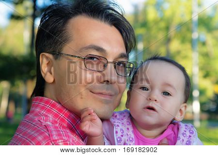 Smiling father and little toddler daughter in a park. Close up portrait