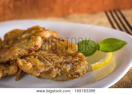 Pork brain pane on plate with lemon and basil