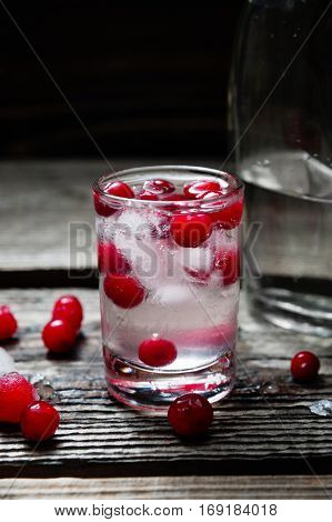 A Bottle and Shot of Vodka with Raspberry on old wooden background