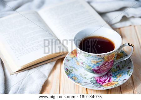 Cozy home still life: cup of hot coffee or tea and opened book with warm plaid closeup