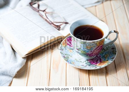 cup of coffee or tea on wooden table with open book and glasses cose up