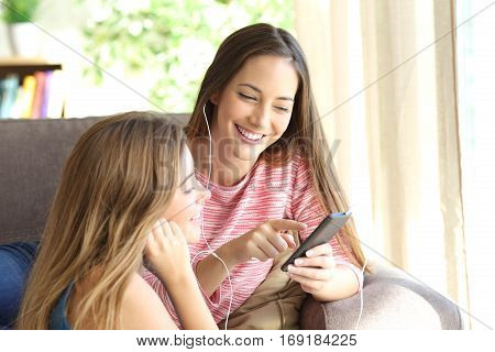 Two friends listening music together online from smart phone sitting on a couch in the living room at home